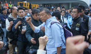 epa08254476 (FILE) - Hong Kong Police arrest media tycoon Jimmy Lai (C) at the main pro-democracy Umbrella Movement site in Admiralty, Hong Kong, China, 11 December 2014 (re-issued 28 February 2020). According to media reports, Apple Daily founder Jimmy Lai was arrested on 28 February and charged with illegal assembly and intimidation, respectively for taking part in an anti-government march in August 2019 and for a clash with a journalist in 2017. Lai is scheduled to appear in court on 5 May 2020 along with two other pro-democracy figures who were arrested the same day.  EPA/STR