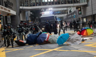 epa08140604 Riot police clear a makeshift barricade during a pro-democracy rally in Hong Kong, China, 19 January 2020. Hong Kong has entered its eighth month of mass protests, originally triggered by a now withdrawn extradition bill, that have since turned into a wider pro-democracy movement.  EPA/JEROME FAVRE