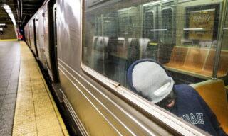 Un uomo dorme nel vagone di una metro deserta a New York, Stati Uniti. EPA/JUSTIN LANE