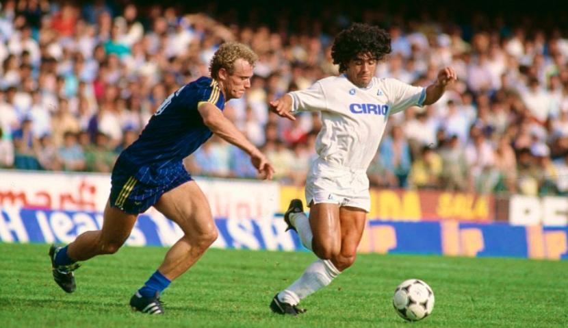 Hans Peter Briegel contende il pallone a Diego Armando Maradona all'esordio in Serie A durante Verona - Napoli allo stadio Bentegodi di Verona, 16 settembre 1984