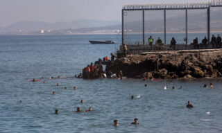 epa09209366 Migrants arrive swimming to cross the border of Tarajal in Ceuta, Spain, 18 May 2021. On the night of 18 May, a total of 5,000 Moroccan nationals entered into the Spanish city of Ceuta, loacted in the North African coast, by sea side and hundreds of migrants continue to attempt doing so. The Spanish authorities have deployed the army to patrol on the border separating Ceuta in the Spanish side from the Moroccan side, in a bid to control this latest surge of entry attempts.  EPA/BRAIS LORENZO
