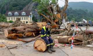 A helper sits during clearing work on the cut trunk of an uprooted tree in the district Kreuzberg of Altenahr, western Germany, on July 17, 2021 after heavy rain hit parts of the country, causing widespread flooding and major damage. - Rescue workers scrambled on July 17 to find survivors and victims of the devastation wreaked by the worst floods to hit western Europe in living memory, which have already left more than 150 people dead and dozens more missing. (Photo by Torsten SILZ / AFP)