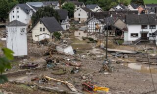 A general view shows houses within a flooded area in Schuld near Bad Neuenahr, western Germany, on July 15, 2021. - Heavy rains and floods lashing western Europe have killed at least 42 people in Germany and left many more missing, as rising waters led several houses to collapse. (Photo by Bernd LAUTER / AFP)