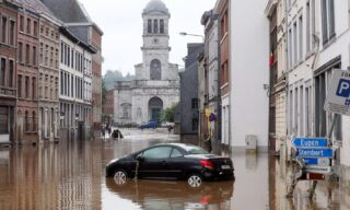 A picture taken on July 15, 2021 shows a car immerged on a flooded street in the Belgian city of Verviers, after heavy rains and floods lashed western Europe, killing at least two people in Belgium. (Photo by François WALSCHAERTS / AFP)