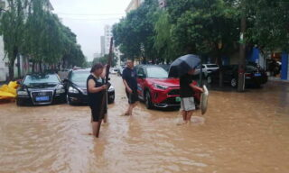 epa09356101 People walk on a flooded road amid heavy rain in Zhengzhou, Henan province, China, 21 July 2021. Heavy floods in Central China killed 12 in Zhengzhou city due to the rainfall yesterday, 20 July 2021, according to official Chinese media. Over 144,660 people have been affected by heavy rains in Henan Province since July 16, and over 10,000 had to be relocated, the provincial flood control and drought relief headquarters said Tuesday.  EPA/Costfoto CHINA OUT