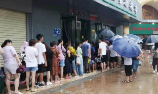epa09356103 People queue on a flooded road amid heavy rain in Zhengzhou, Henan province, China, 21 July 2021. Heavy floods in Central China killed 12 in Zhengzhou city due to the rainfall yesterday, 20 July 2021, according to official Chinese media. Over 144,660 people have been affected by heavy rains in Henan Province since July 16, and over 10,000 had to be relocated, the provincial flood control and drought relief headquarters said Tuesday.  EPA/Costfoto CHINA OUT