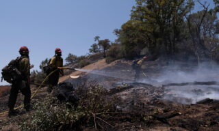 epa09345043 Hot Shots Big Bear crew perform mop up duties on a hillside situated along Road 600 in Raymond, CA as firefighters battle The River Fire in the high Sierra foothills of Madera and Mariposa counties outside of Oakhurst, California, USA, 14 July 2021.  EPA/DAVID ODISHO