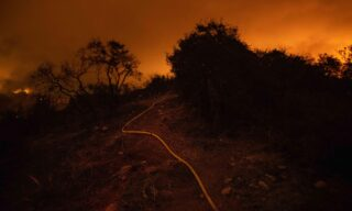 epa09203506 Fire surrounds a water hose as firefighters attempt to reach the Palisades Fire in Topanga, California, USA, 15 May 2021. The fire had burned over 700 acres by nightfall, prompting evacuations.  EPA/CHRISTIAN MONTERROSA