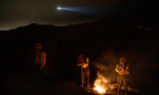 epa09203507 Firefighters stay warm by a small fire as they keep an eye on the Palisades Fire in Topanga, California, USA, 15 May 2021. The fire had burned over 700 acres by nightfall, prompting evacuations.  EPA/CHRISTIAN MONTERROSA